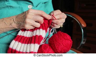 closeup of old womans hands knittin