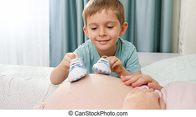 Closeup of older son walking with baby boots acroos big belly of pregnant mother lying on bed at bedroom