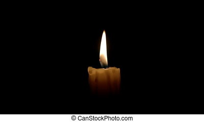 Closeup of one candle on black backgrounds.