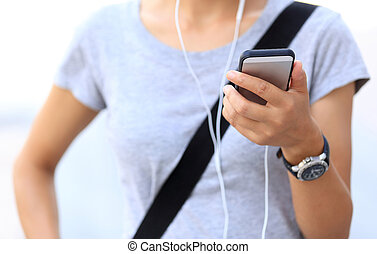 closeup of one young asian woman use smartphone listening music