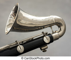 closeup of part of bass clarinet with grey background