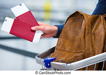 Closeup of passport and boarding ticket and a backpack in the luggage trolleys