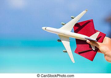 Closeup of passports and white miniature airplane background the turquoise sea