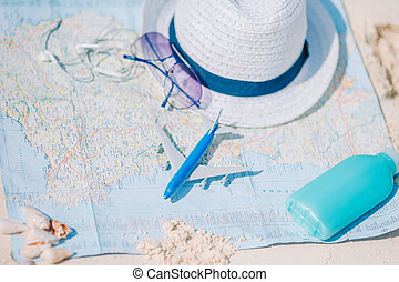 Closeup of passports, toy airplane, sunglasses on the map