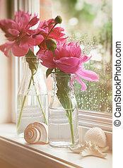Closeup of peony flowers in milk bottles