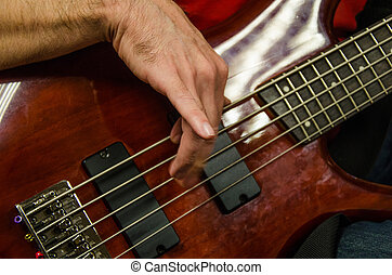 Closeup of photo of electric bass guitar player