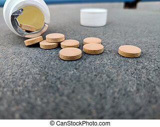 Closeup of Pill bottle with orange pills on stone background. Selective focus