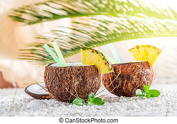 Closeup of pinacolada in coconut on sandy beach