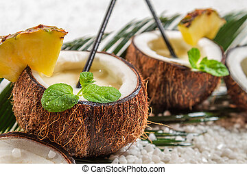 Closeup of pinacolada with mint leaf in the coconut