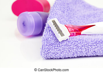 Closeup of pink shaving blade on towel with moisturizer -...