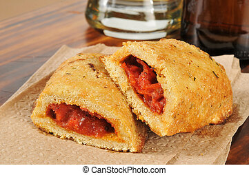 Calzones or pizza pockets and a mug of beer