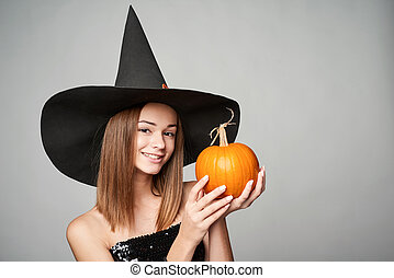 Closeup of playful Halloween witch holding pumpkin - Closeup...