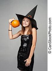 Closeup of playful Halloween witch holding pumpkin - Smiling...