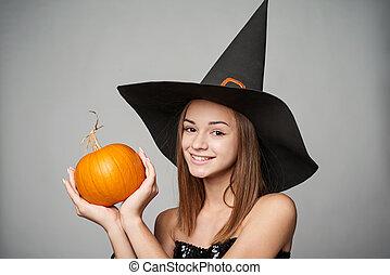 Closeup of playful Halloween witch holding pumpkins -...