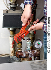 Closeup of plumber turning heating system valve with red...