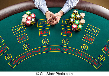 Close up of poker player with chips at green casino table, view from above.