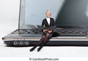 Closeup of pretty blond lady sitting on a laptop