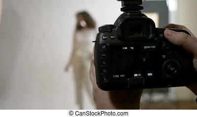 Closeup of professional DSLR camera photographing an...