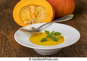 closeup of pumpkin soup on wood