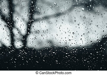 Closeup of rain droplets on glass window, water droplets with light reflection and refraction, blurred dark autumn landscape, black and white abstract background