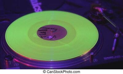 """Closeup of record rotating on deejay turntable, lights flashing"""