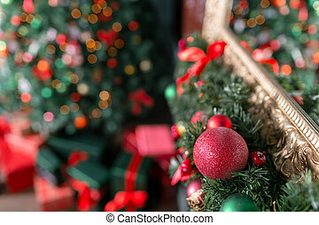 Closeup of red and green bauble hanging from a decorated Christmas branch. abstract background with defocused lights