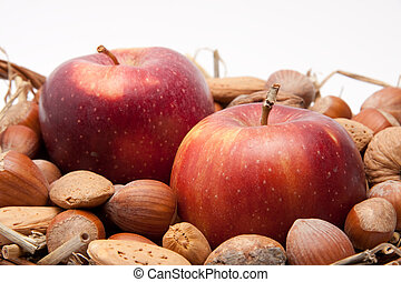 red apples and nuts in a basket isolated on white background