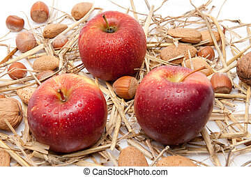 closeup of red apples with waterdrops and nuts isolated on white background