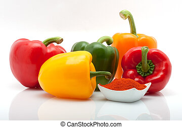 red, green, yellow and orange peppers and paprika in a dish isolated on white background