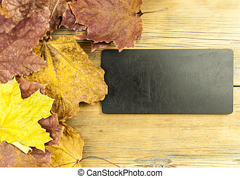 Closeup of red maple leaf with blank blackboard on old wood plank  Top view