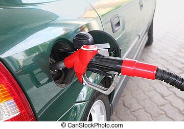 closeup of red pump for refueling filling green car on station