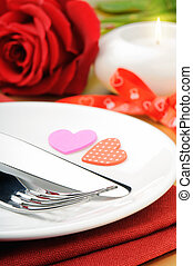 Closeup of red rose and cutlery