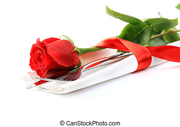 Closeup of red rose and cutlery on white