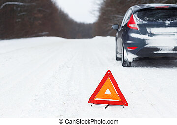 Closeup of red warning triangle with a broken down car