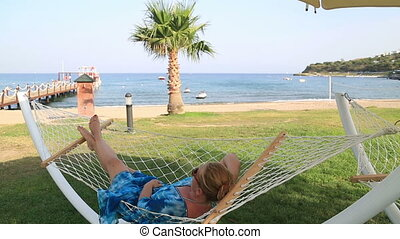 Closeup Of Relaxing Woman In Hammock - Middle aged blonde...