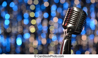 Closeup of retro microphone with blurred lights at background, sliding video