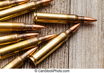 Closeup of rifle full metal jacket bullets on wooden background