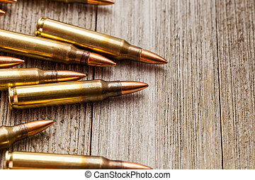 Closeup of rifle full metal jacket bullets on wooden background with copy space