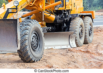 Closeup of road grader blade - Large yellow road grader ...