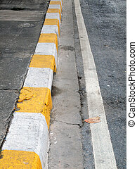 closeup of road with yellow and white line
