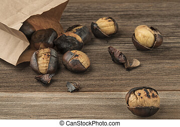 roasted chestnuts in a paper bag on a wooden table
