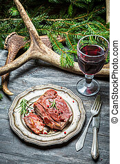 Closeup of roasted venison with red wine