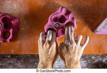 Closeup of rock climber's hands gripping handhold in indoor...