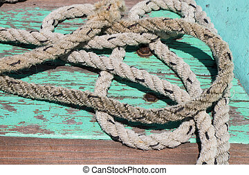 Closeup of rope on teal ship deck.