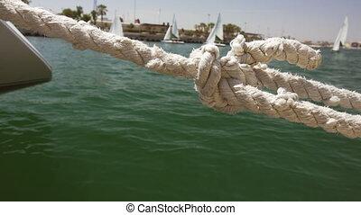 Closeup of sailboat rope in marina with small - Sailboat...