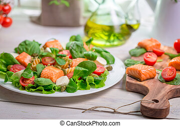 Closeup of salad with fresh vegetables and salmon