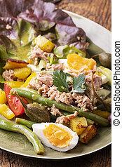 closeup of salade nicoise on dark wood