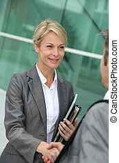 Closeup of sales woman shaking hand to business patner