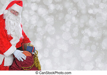 Closeup of Santa Claus with his bag of toys over a silver bokeh background