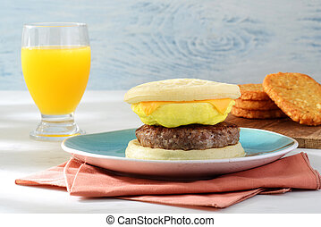 sausage egg cheese waffles sandwich with glass of orange juice